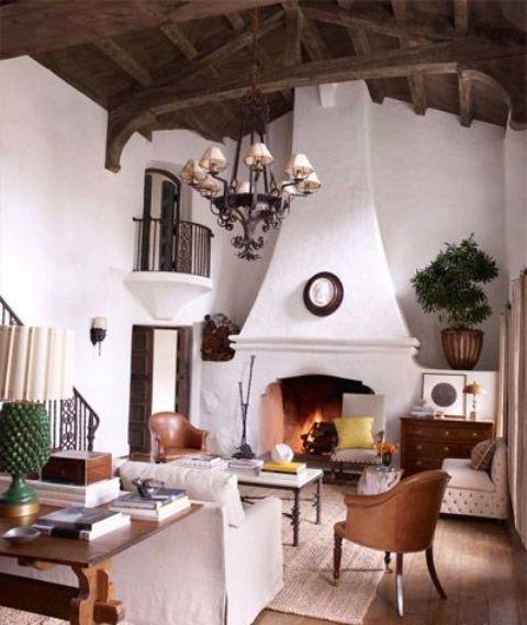 un salon espagnol chic mais petit avec des murs en plâtre blanc, une grande cheminée, des accents colorés et des chaises en cuir