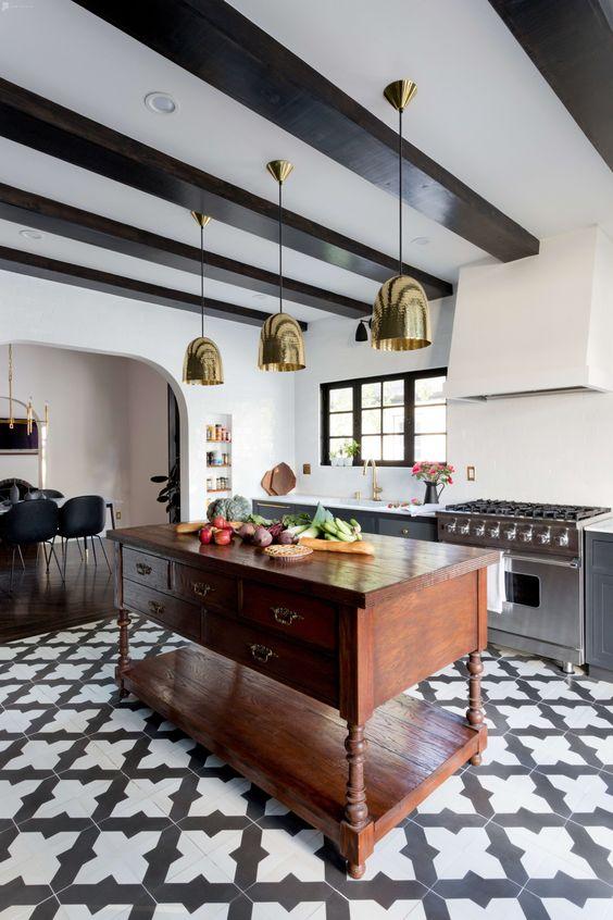 une cuisine espagnole moderne avec des carreaux imprimés, des suspensions en or, de lourds meubles en bois et des poutres en bois sombres