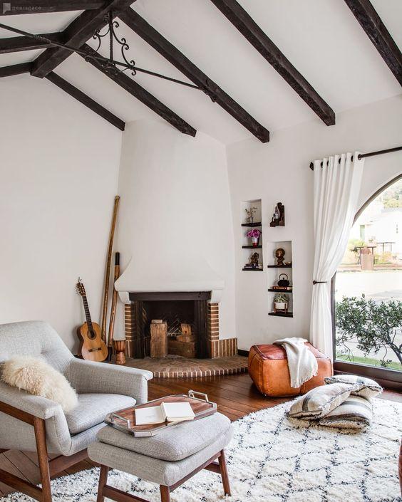 un salon moderne et contemporain avec des murs blancs et un plafond, des poutres en bois sombres, une cheminée chic et des touches de bois et de cuir