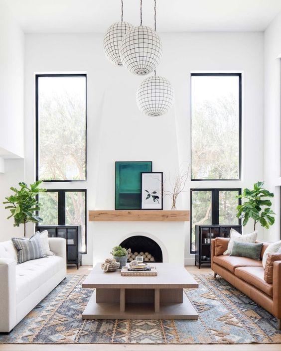 un espace espagnol moderne avec des murs blancs, une fausse cheminée, des meubles aux couleurs chaudes et des touches et des imprimés lumineux