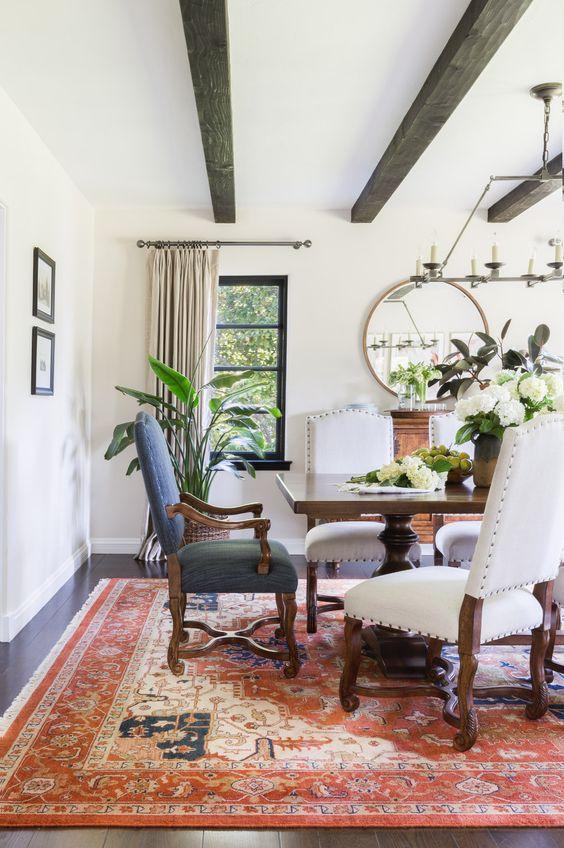 une salle à manger espagnole avec de lourds meubles en bois sombre, un tapis imprimé, un miroir rond et beaucoup de verdure et de fleurs