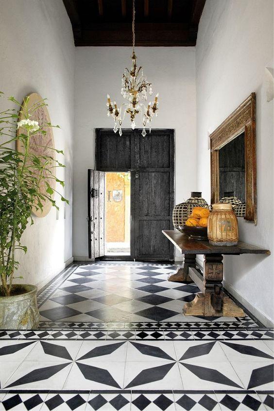 une entrée espagnole avec des carreaux imprimés en noir et blanc, une porte en bois de Dakr récupéré, une console lourde et de la verdure en pot