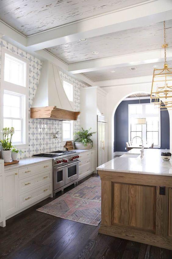 une cuisine espagnole moderne avec un dosseret de carreaux imprimés, un îlot de cuisine en bois épais et un plafond blanc avec des poutres