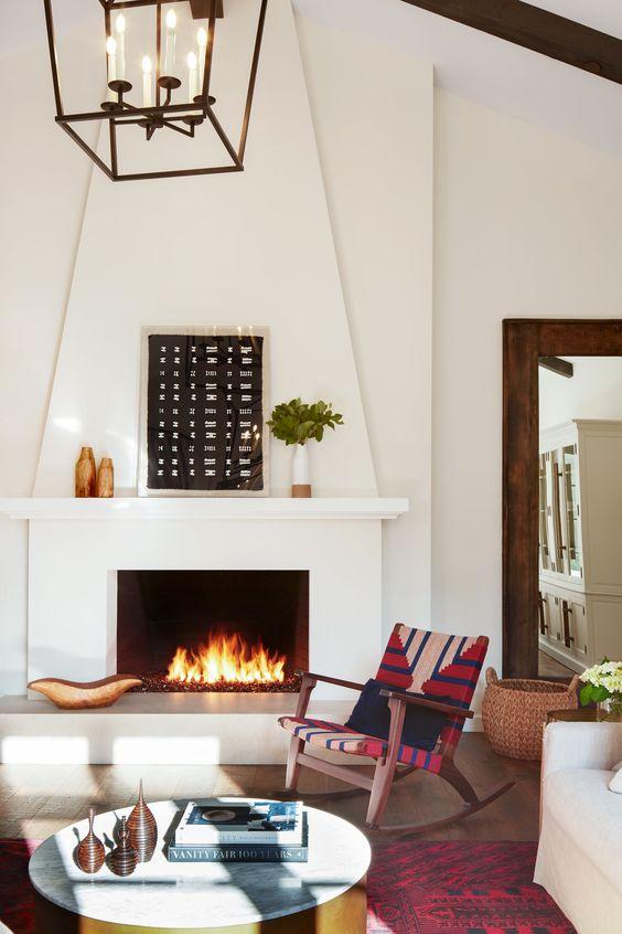 un salon espagnol avec des murs blancs et une grande cheminée, des textiles imprimés aux couleurs vives et des œuvres aux couleurs chaudes