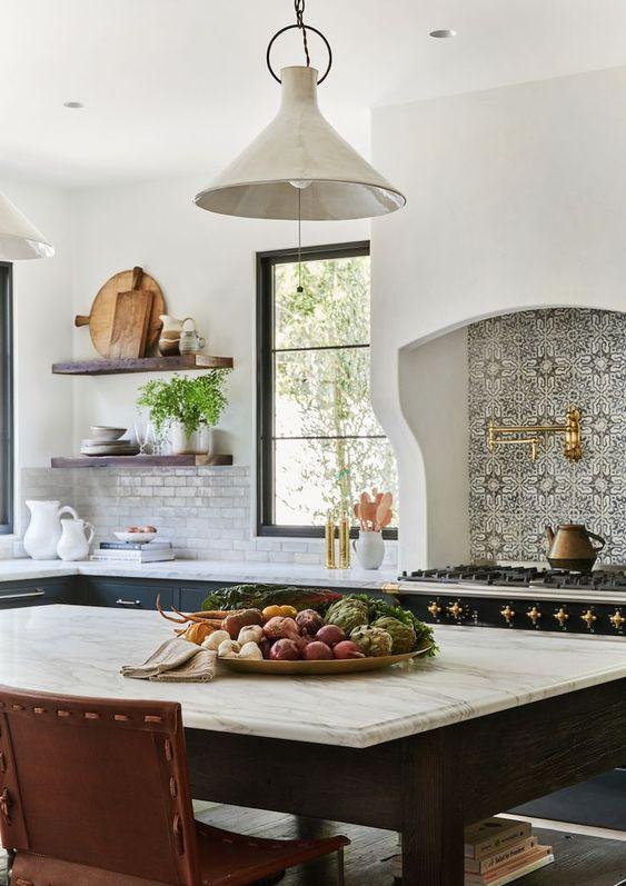 une cuisine espagnole avec une grande cuisinière, un dosseret imprimé, des touches dorées, des meubles sombres et des lampes à l'esprit vintage