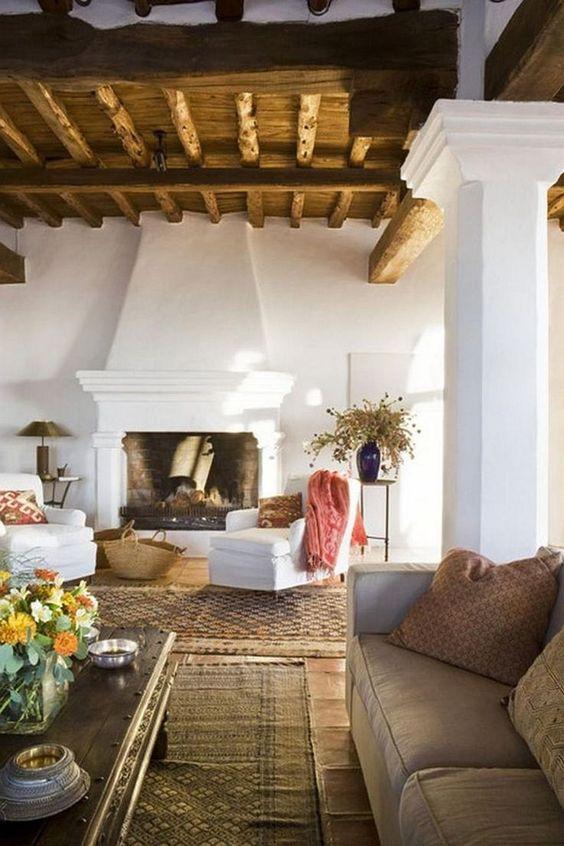 un salon espagnol avec des murs en plâtre blanc, un plafond en bois avec des poutres, des tapis en couches et des accents frais et lumineux