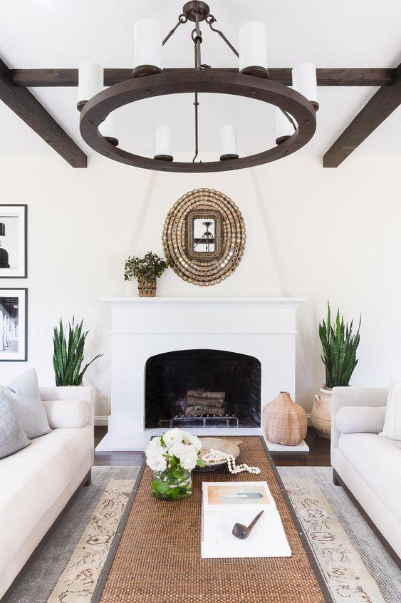un salon espagnol avec des murs blancs, des poutres en bois sombres, un lustre assorti, une cheminée et des touches naturelles