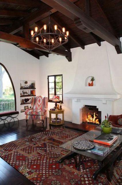 un salon espagnol avec des murs en plâtre blanc, un plafond sombre avec des poutres, une grande cheminée et des textiles et des tissus d'ameublement imprimés