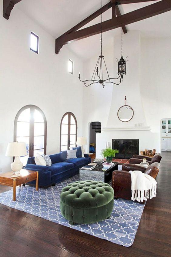 un salon espagnol avec des murs blancs et un plafond à double hauteur, des poutres en bois sombres, une grande cheminée et des meubles aux tons bijou