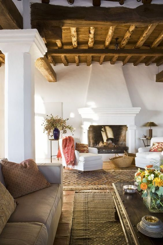 un salon espagnol avec un plafond en bois avec des poutres, des murs blancs et une cheminée, des meubles neutres et des fleurs séchées