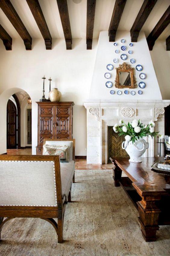 un salon espagnol avec des murs blancs, des sols carrelés, des poutres en bois sombres, des meubles élégants et lourds et une grande cheminée