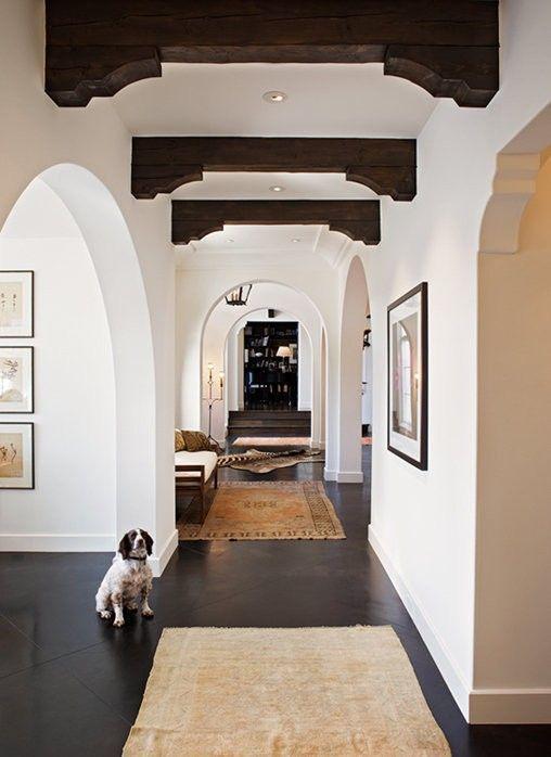 les murs de plâtre blanc associés à des sols sombres et des poutres en bois sombres ainsi que des portes cintrées ressemblent beaucoup à l'espagnol