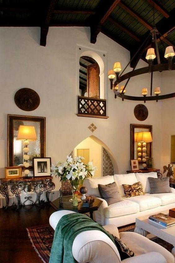 une chambre de style espagnol avec des murs blancs, des portes cintrées, des meubles neutres, des lampes vintage et des lustres