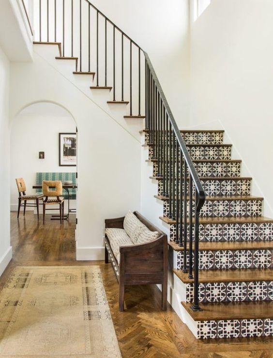 un espace d'inspiration espagnole avec des carreaux imprimés sur les escaliers, des meubles et des sols en bois et une balustrade forgée
