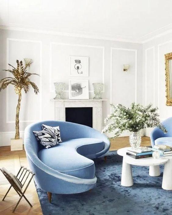un salon charmant avec un canapé bleu incurvé et des chaises assorties et une table audacieuse qui attire le regard
