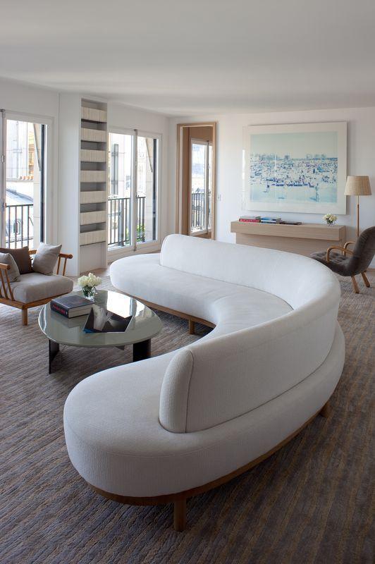 un magnifique canapé blanc incurvé envahit tout le salon et y ajoute des lignes et des formes douces