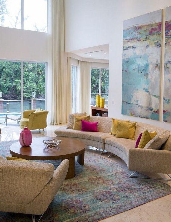 un salon moderne du milieu du siècle avec un canapé incurvé, des oreillers colorés et une aquarelle pour plus de couleur