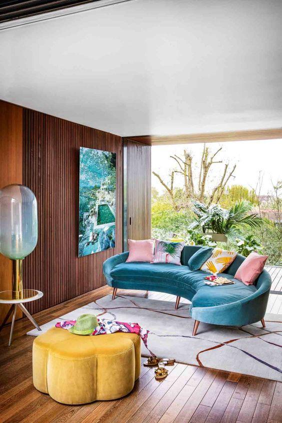 un salon tropical coloré avec un canapé incurvé bleu vif, un pouf en forme de fleur jaune vif et une œuvre d'art audacieuse