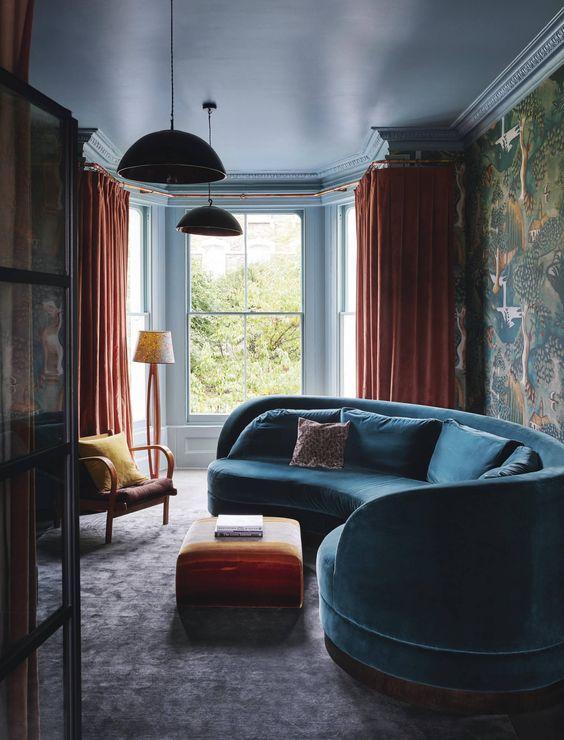 un salon maussade et audacieux avec un canapé bleu incurvé, des textiles orange et du papier peint à imprimé oiseau maussade sur un mur