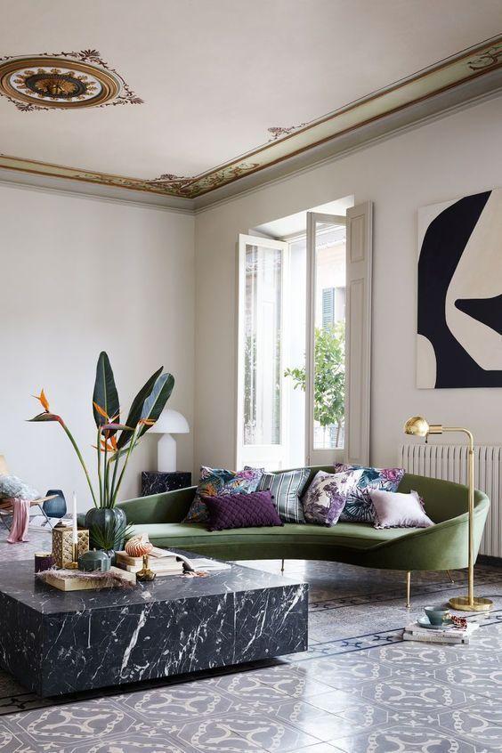 un salon chic et raffiné fait avec du carrelage, une table basse en marbre noir et un chic canapé courbé vert comme pièce maîtresse