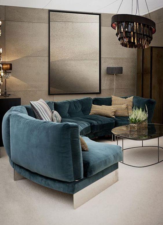 un salon raffiné et maussade avec un canapé turquoise incurvé qui ajoute de la couleur à l'espace et le rend plus audacieux