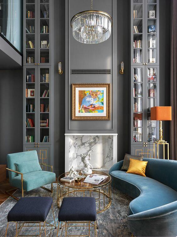 un salon raffiné avec un canapé bleu incurvé qui occupe tout l'espace et des touches de souci et d'orange