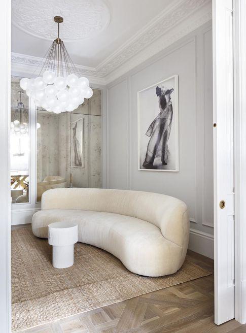 un espace neutre et raffiné avec un canapé neutre incurvé qui attire le regard par sa forme et ajoute une sensation chic