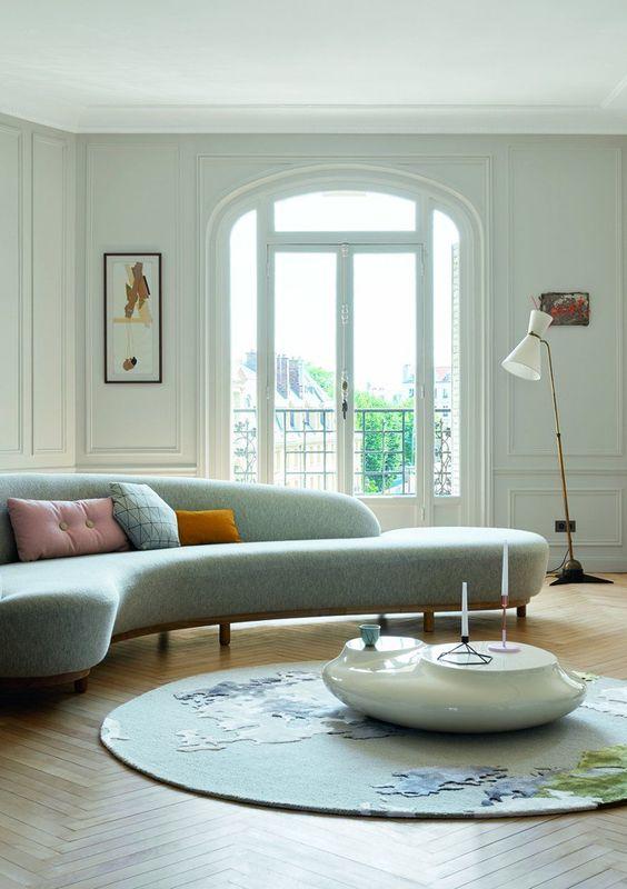 un salon éthéré avec un canapé bleu incurvé, un tapis abstrait et une table basse en galets blancs