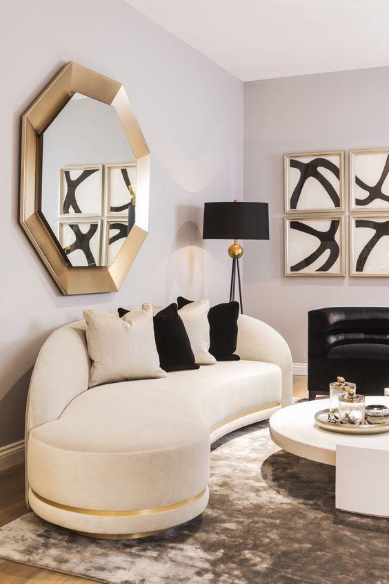 un espace raffiné avec un canapé incurvé blanc et noir, des touches dorées et des œuvres d'art audacieuses est un salon étonnant