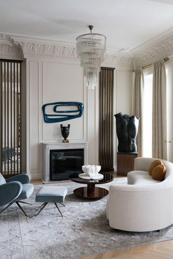 un salon raffiné avec un canapé blanc incurvé et un décor accrocheur et des œuvres d'art qui perpétuent le style unique de la pièce