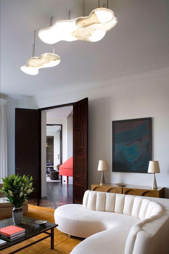 un espace exquis avec un canapé incurvé blanc et des plafonniers qui ressemblent à ce canapé en forme