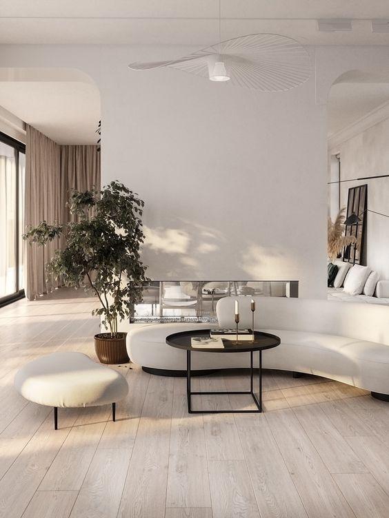 un élégant salon minimaliste avec un canapé incurvé et un repose-pieds assorti ainsi qu'une table basse ronde noire