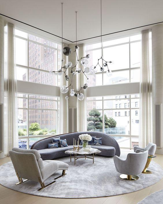un élégant salon à double hauteur avec un canapé bleu incurvé et des chaises assorties ainsi que des touches dorées ici et là