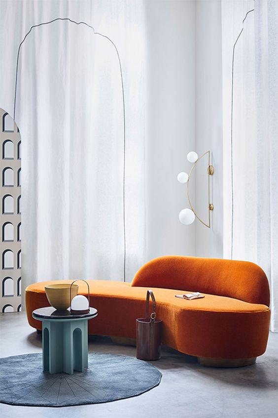 un salon conceptuel audacieux avec un canapé orange incurvé, un tapis rond bleu et une table turquoise pour une configuration audacieuse