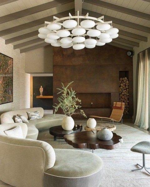 un salon chic avec un long canapé incurvé blanc, une table basse en tranches de bois et une cheminée revêtue de métal