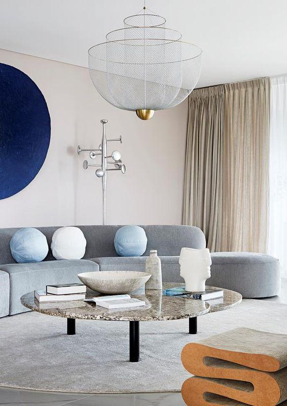 un salon neutre rendu audacieux avec un canapé gris incurvé, une œuvre d'art marine et une table basse en marbre et un tabouret en liège