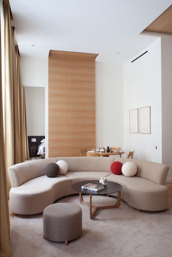 un petit salon plus audacieux avec un canapé incurvé qui sépare également le salon et l'espace salle à manger
