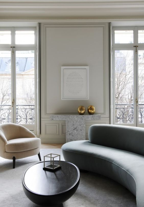 un salon minimaliste exquis avec un canapé incurvé gris et une chaise blanche assortie ainsi qu'une table incurvée pour adoucir l'espace