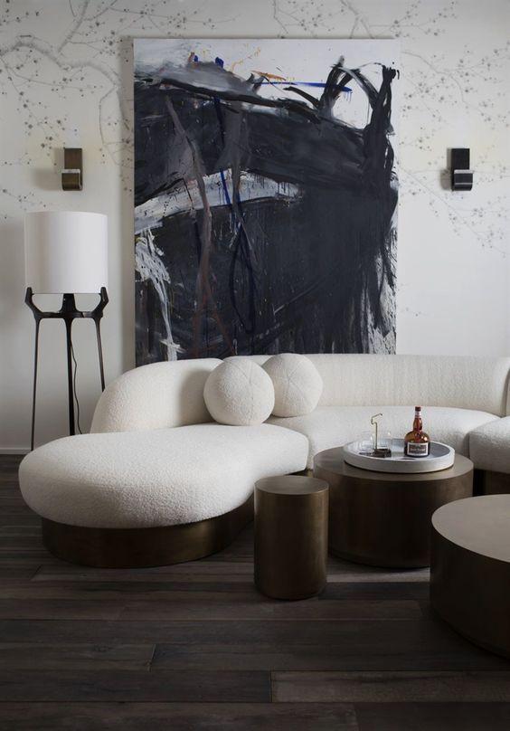 un salon monochromatique avec un canapé incurvé crémeux et des oreillers ronds et des tables rondes en métal foncé