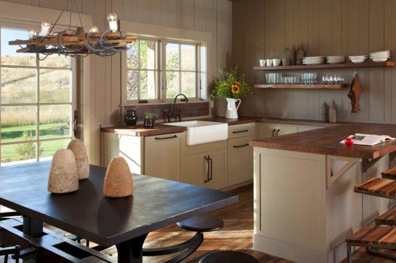 La cuisine est faite avec des armoires en bois blanc avec des comptoirs en bois, il y a un espace repas avec des meubles sombres
