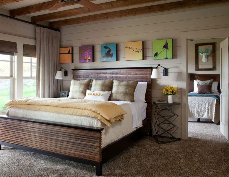 La chambre est aménagée avec un lit en ardoise en bois, des œuvres d'art colorées, des tables d'appoint en métal