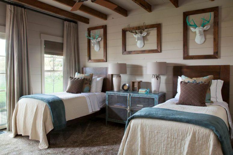 Cette chambre d'amis est faite avec une crédence bleue avec des portes transparentes, de fausses têtes de cerfs accrocheuses et des lits assortis