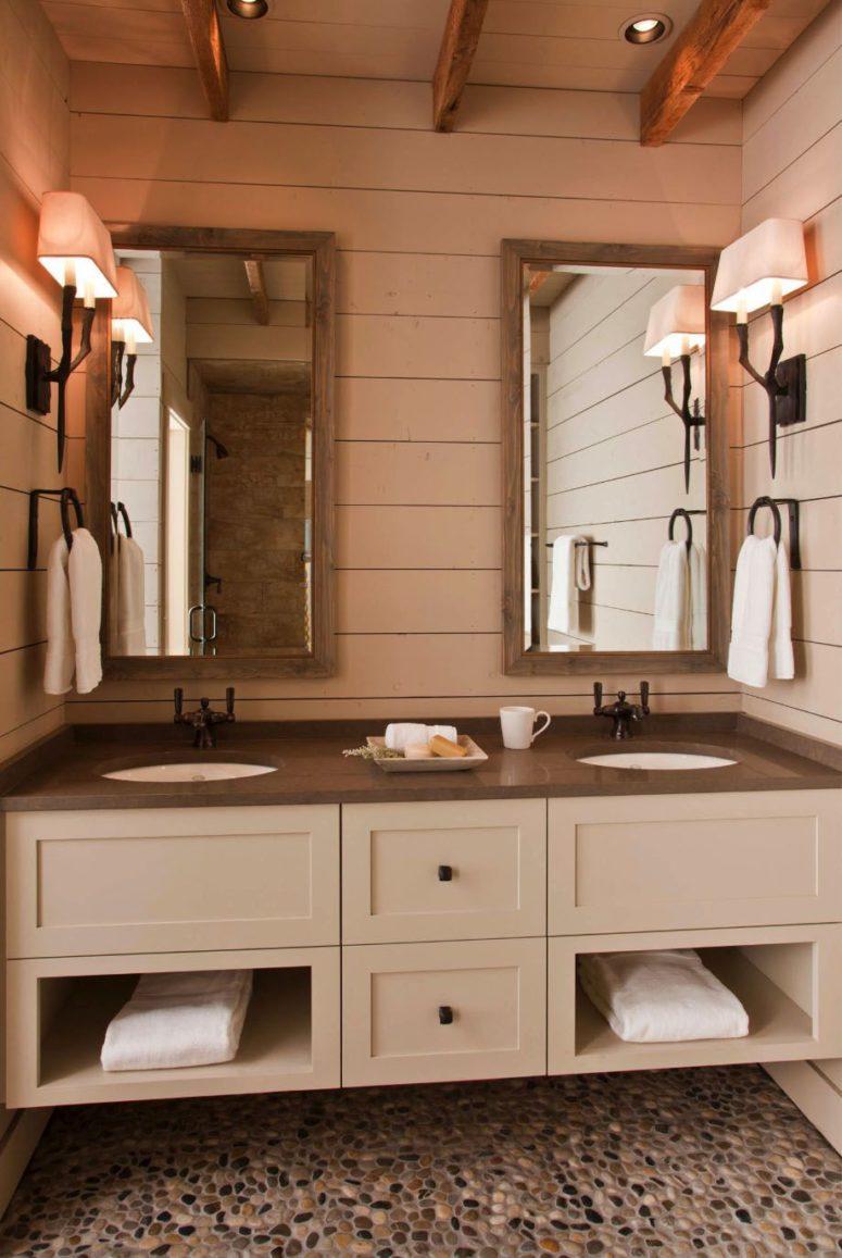 La salle de bain est faite dans des tons neutres, avec des comptoirs sombres et des miroirs dans des cadres en bois