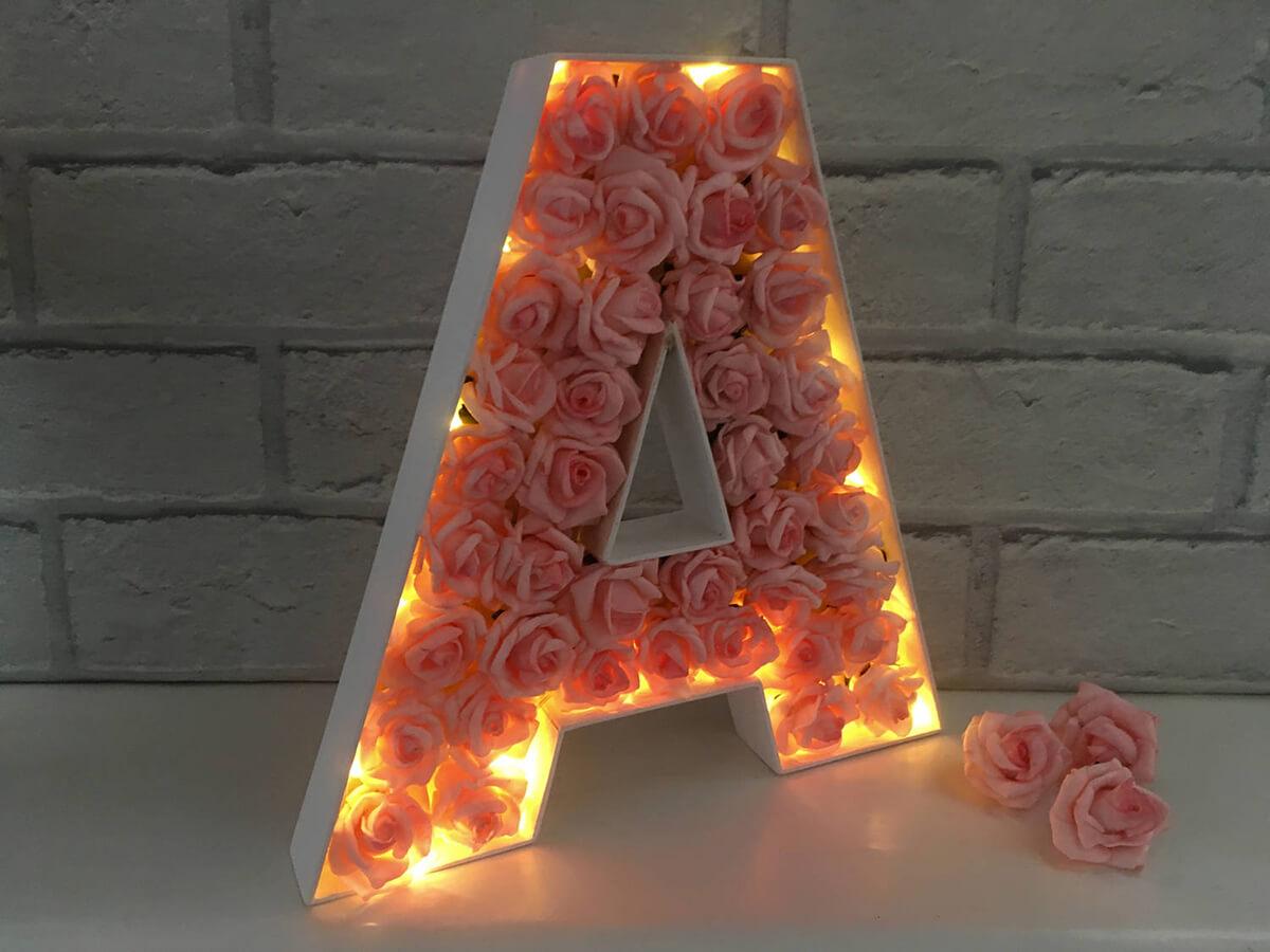 Lettre lumineuse infusée de boutons de roses roses