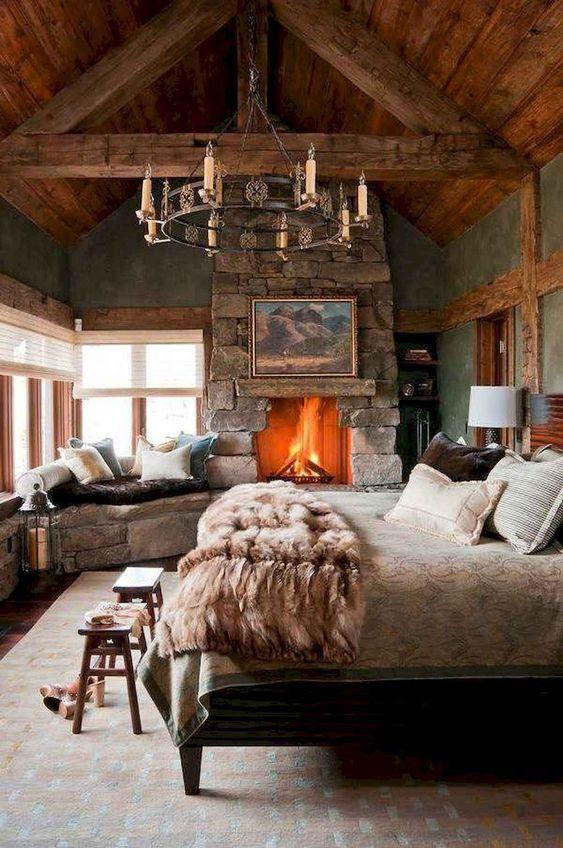 une chambre cabine avec une cheminée en pierre brute et un banc, un lustre accrocheur, des articles en bois et des draps confortables