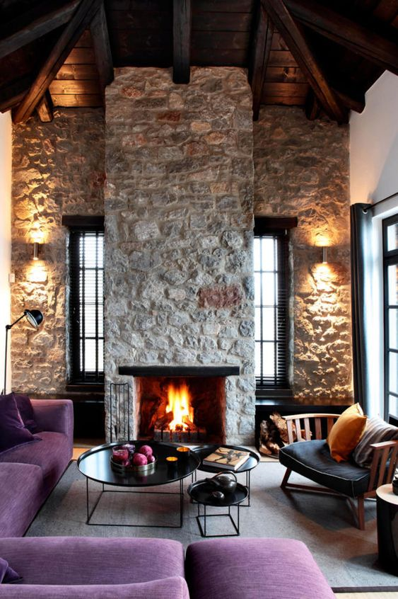 un salon contemporain lumineux avec des murs en pierre brute et une cheminée, des meubles violets et d'élégantes tables rondes