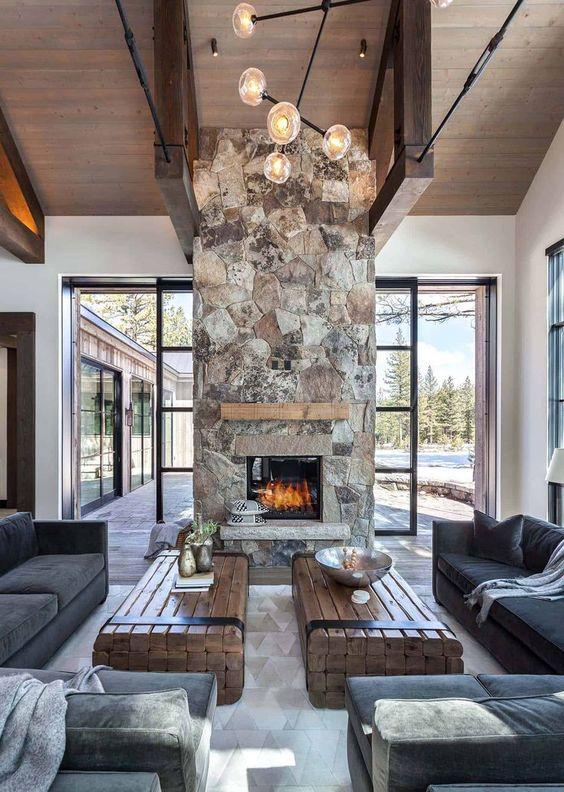 un espace cabine chic et contemporain avec des meubles sombres, des tables en dalle de bois et une cheminée en pierre spectaculaire avec un manteau en bois
