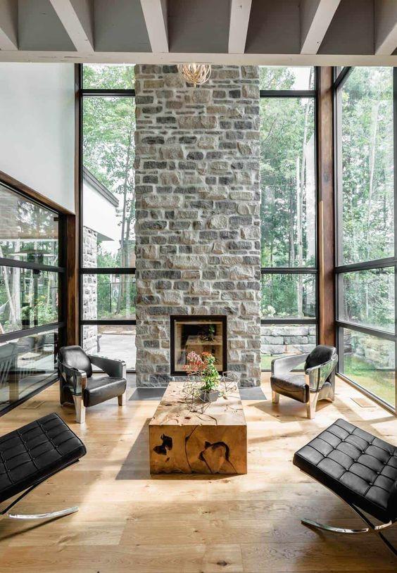 un salon contemporain chic avec une cheminée en pierre comme pièce maîtresse, des chaises en cuir noir et une table en dalle de bois