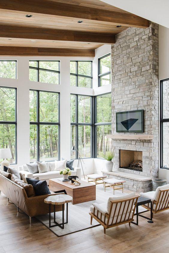 un salon double hauteur propre et moderne avec une cheminée en pierre grise et un manteau en bois comme pièce maîtresse