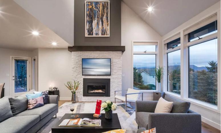 un salon moderne et propre dans des tons clairs et une cheminée encastrée revêtue de fausse pierre blanche assortie